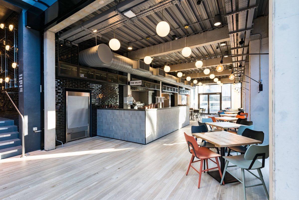 modern blue and grey coffee shop with orange, grey, and blue chairs and square table
